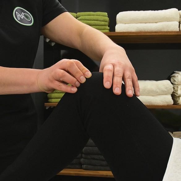 Osteopath treating knee pain.