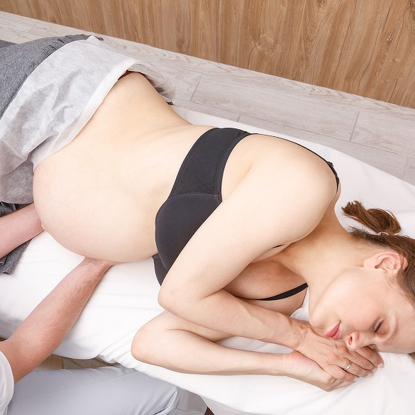 Pregnant woman receiving osteopathic treatment.