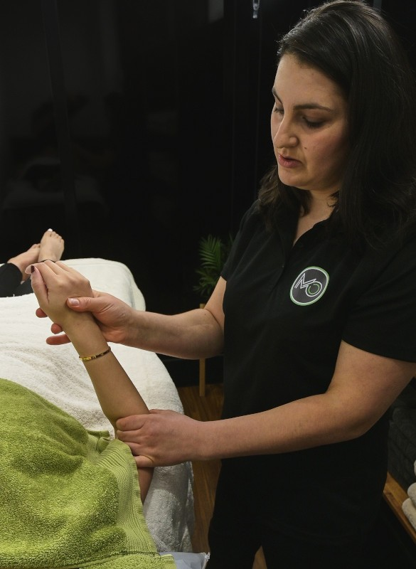 Moreland Osteopathy treating a woman's forearm and wrist.